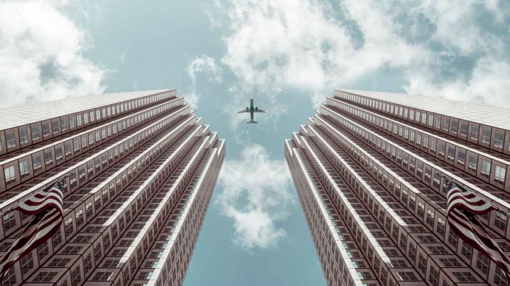 worm s eye view photo of plane between two high rise buildings